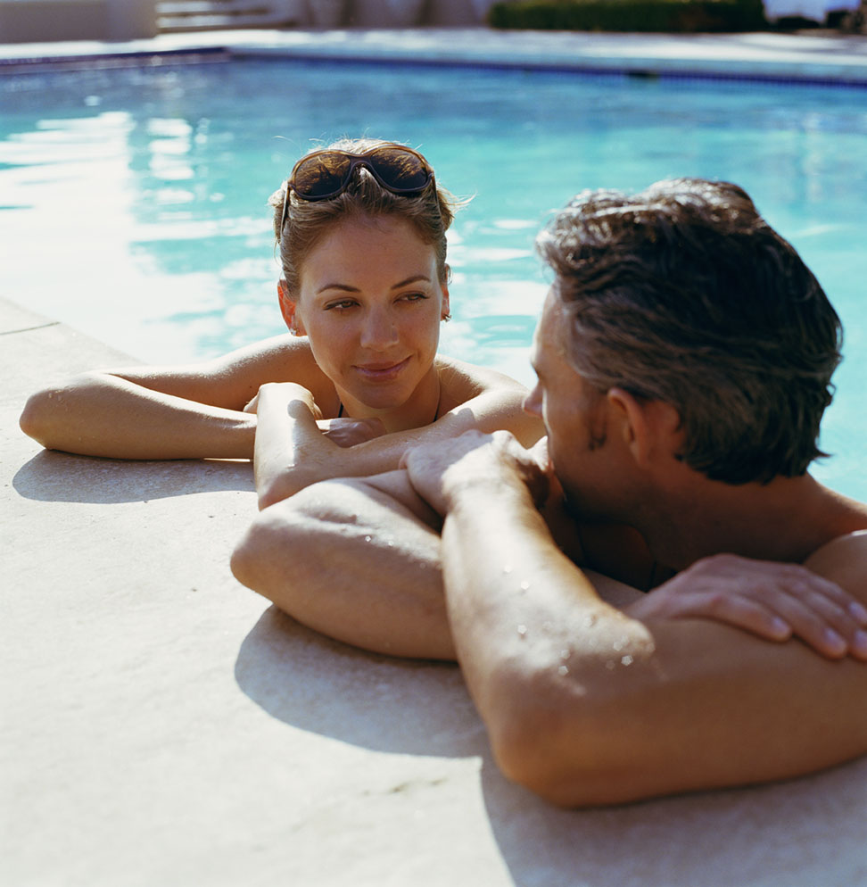 Couple talking in pool, resting arms on side wall