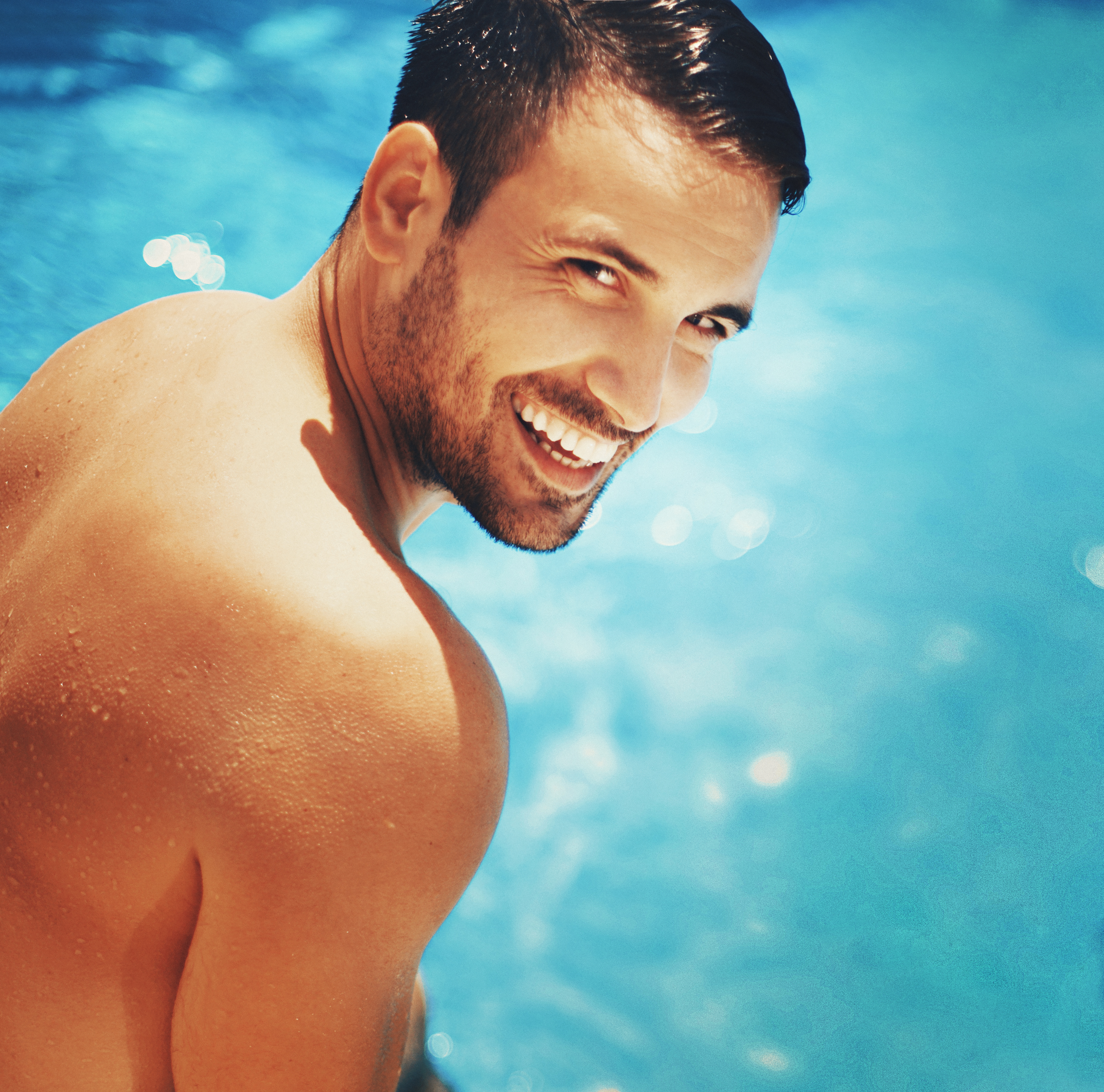 Handsome man relaxing by swimming pool.